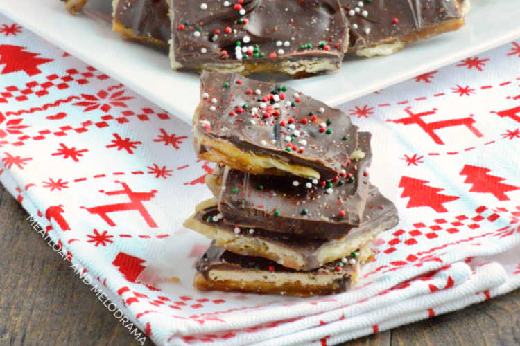 easy saltine toffee christmas crack with sprinkles stacked on a holiday towel