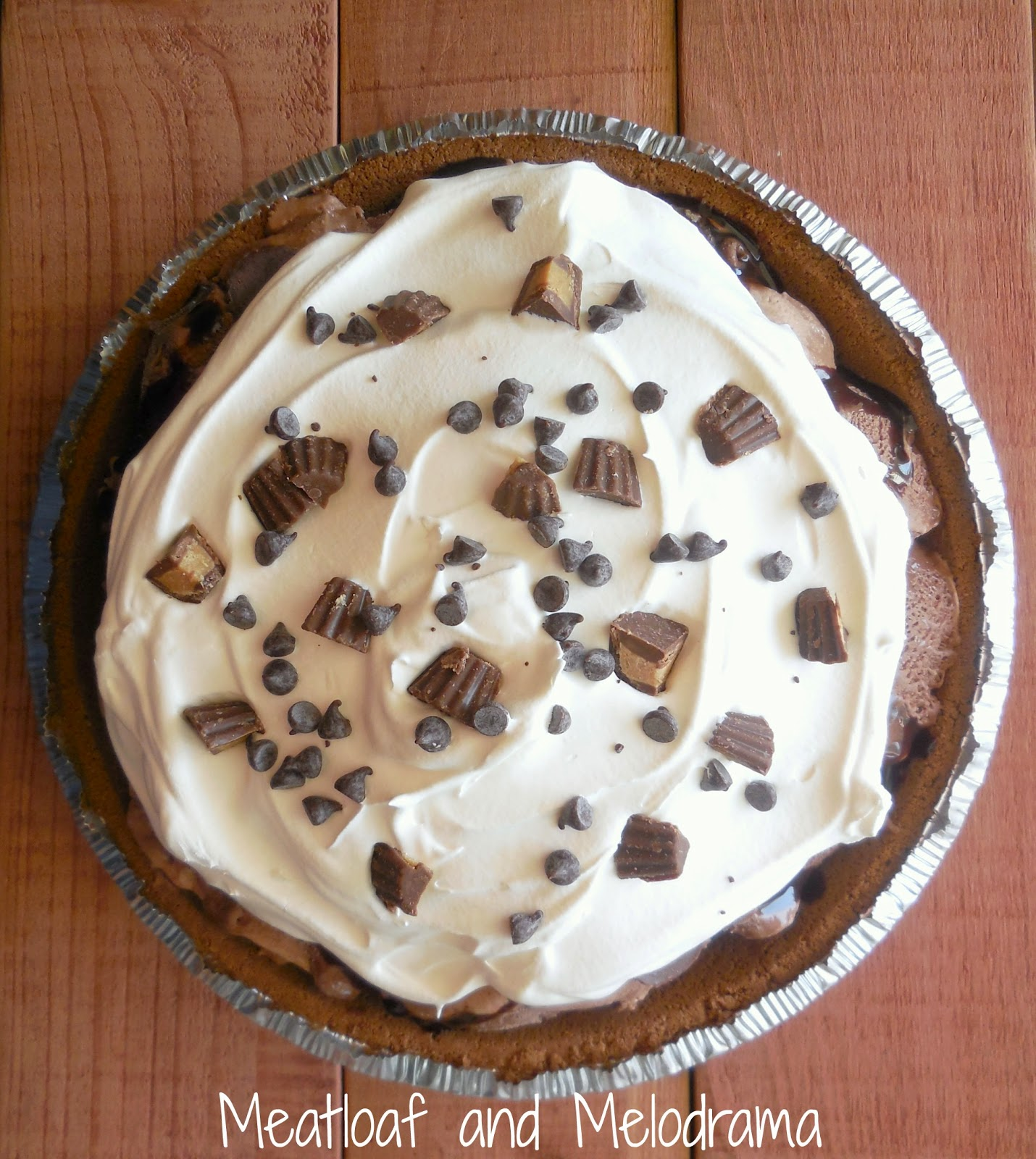 chocolate ice cream pie with whipped topping, chocolate chips and reese's cups on top