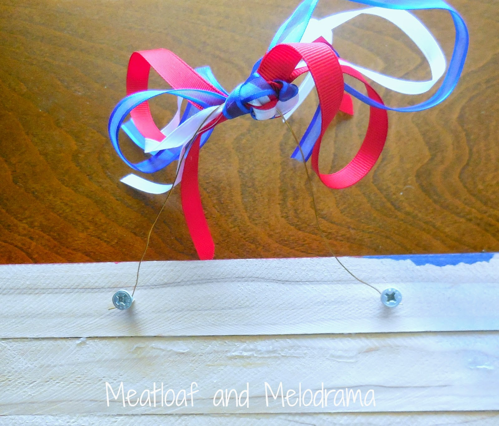 attach wire to back of flag with screws and add ribbon