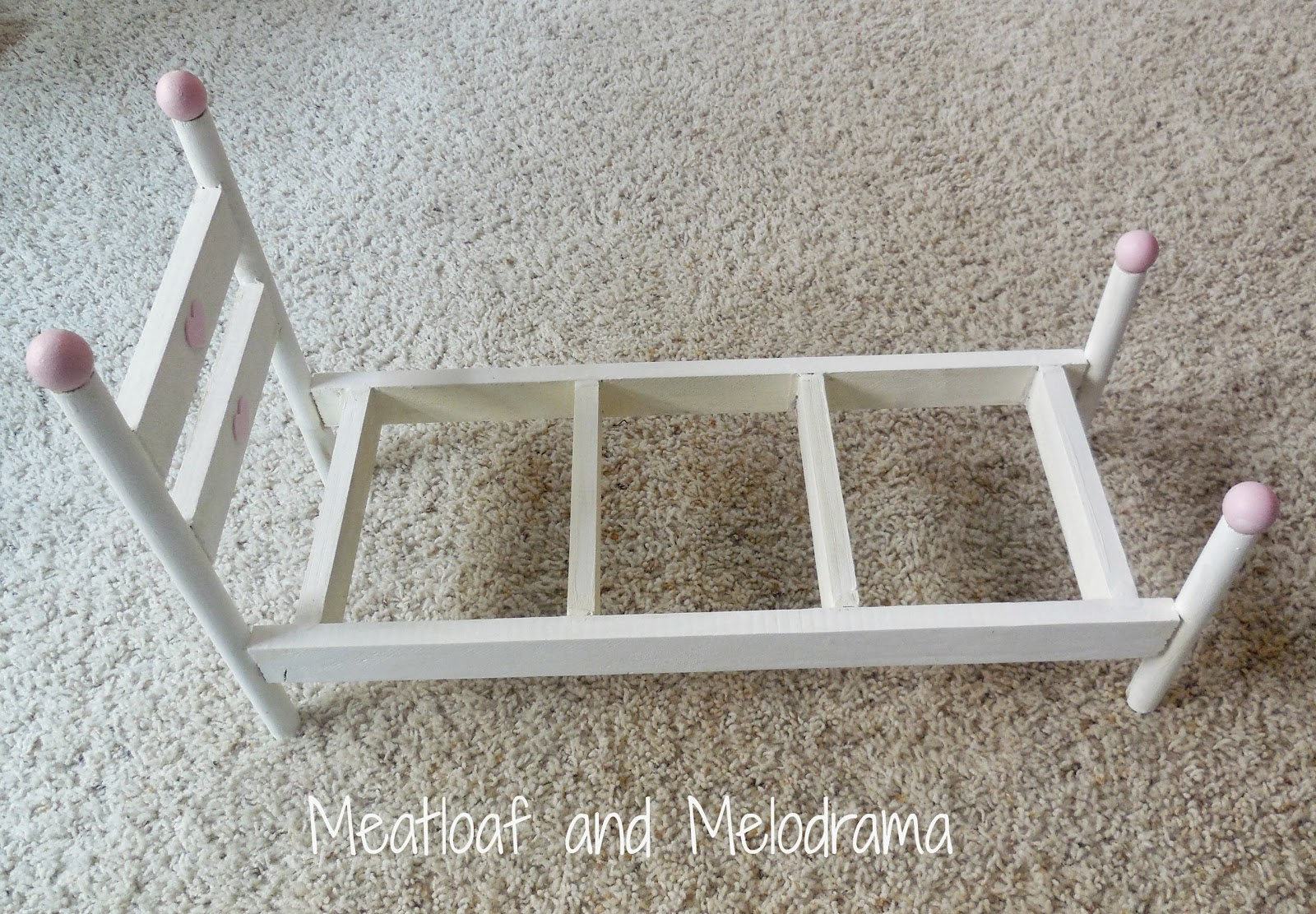 white and pink doll bed made from garden stakes and dowel rods