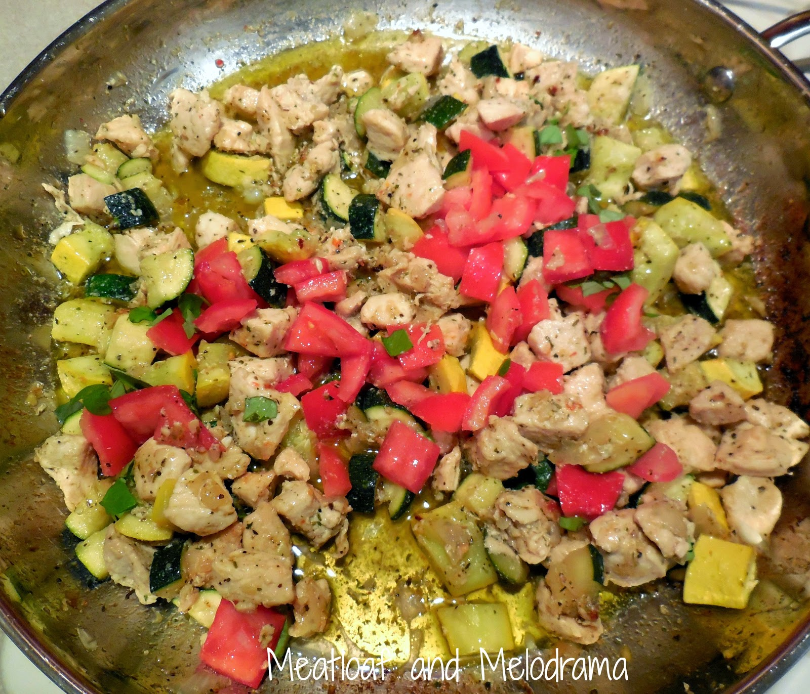 sauteed chicken in pan with zucchini, summer squash and tomatoes