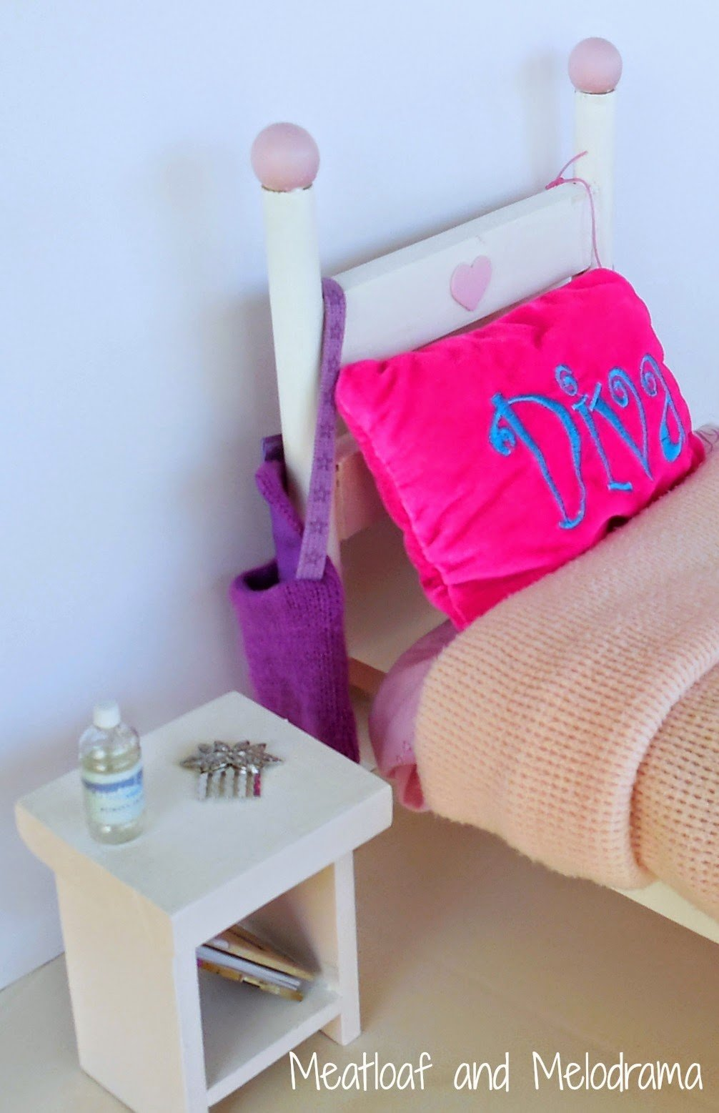 pink and white American Girl doll bed and nightstand with diva pillow
