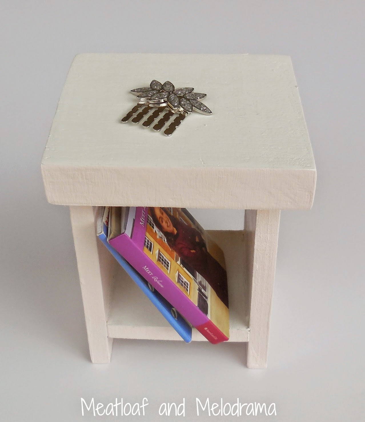pink and white doll nightstand made from wood with books