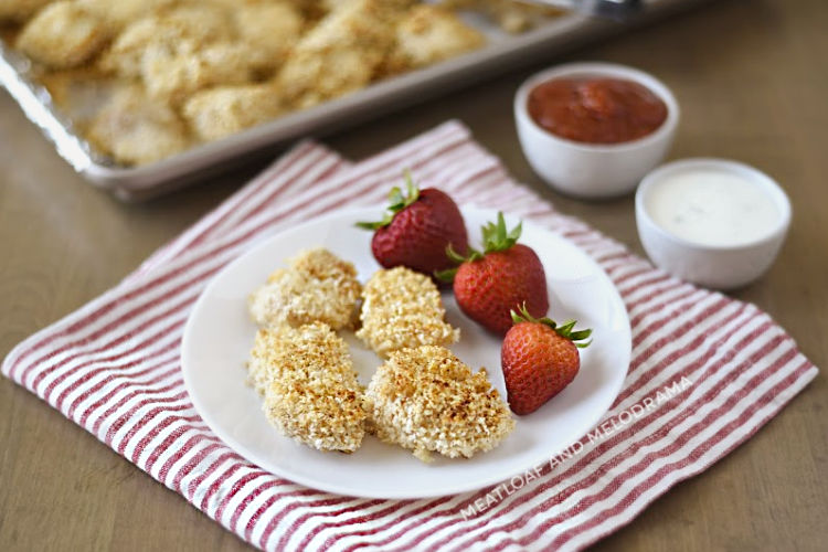 baked homemade chicken nuggets with panko on a white plate with strawberries