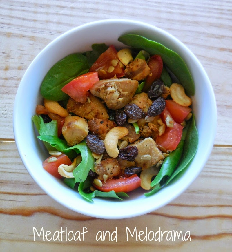 cooked chicken over salad greens with tomatoes, raisins and nuts
