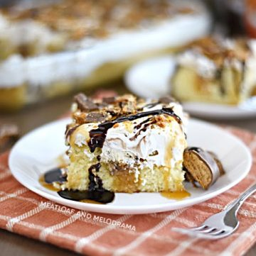 slice of butterfinger poke cake with cool whip frosting on a white platel