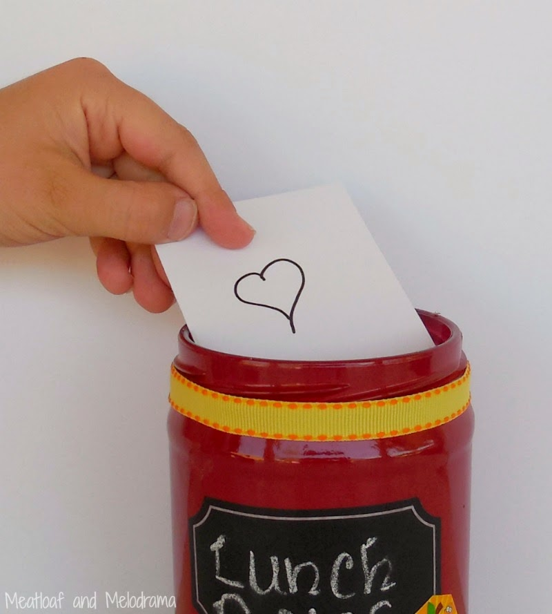 old salsa jar spray painted red with chalkboard label and yellow ribbon for holding notes.