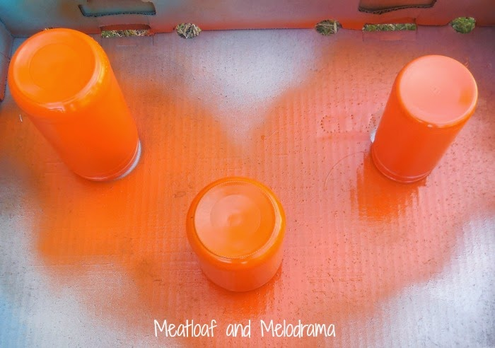 spray paint three glass jars orange