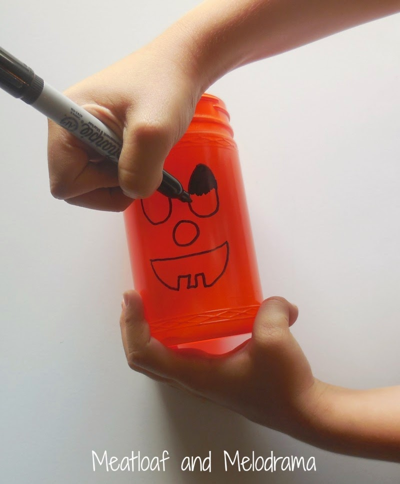 draw face on orange jar with sharpie marker