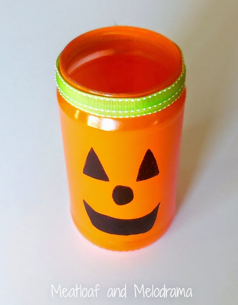 orange spray paint glass jar with jack o lantern face and green ribbon