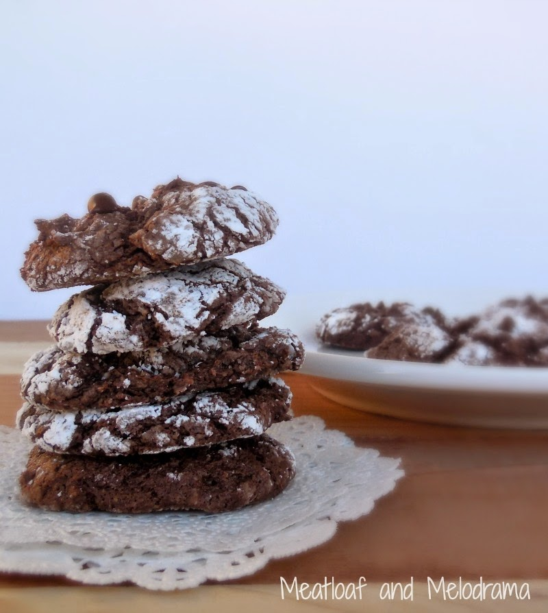 stack of chocolate crinkle cookies with powdered sugar on a doily made with cool whip and cake mix