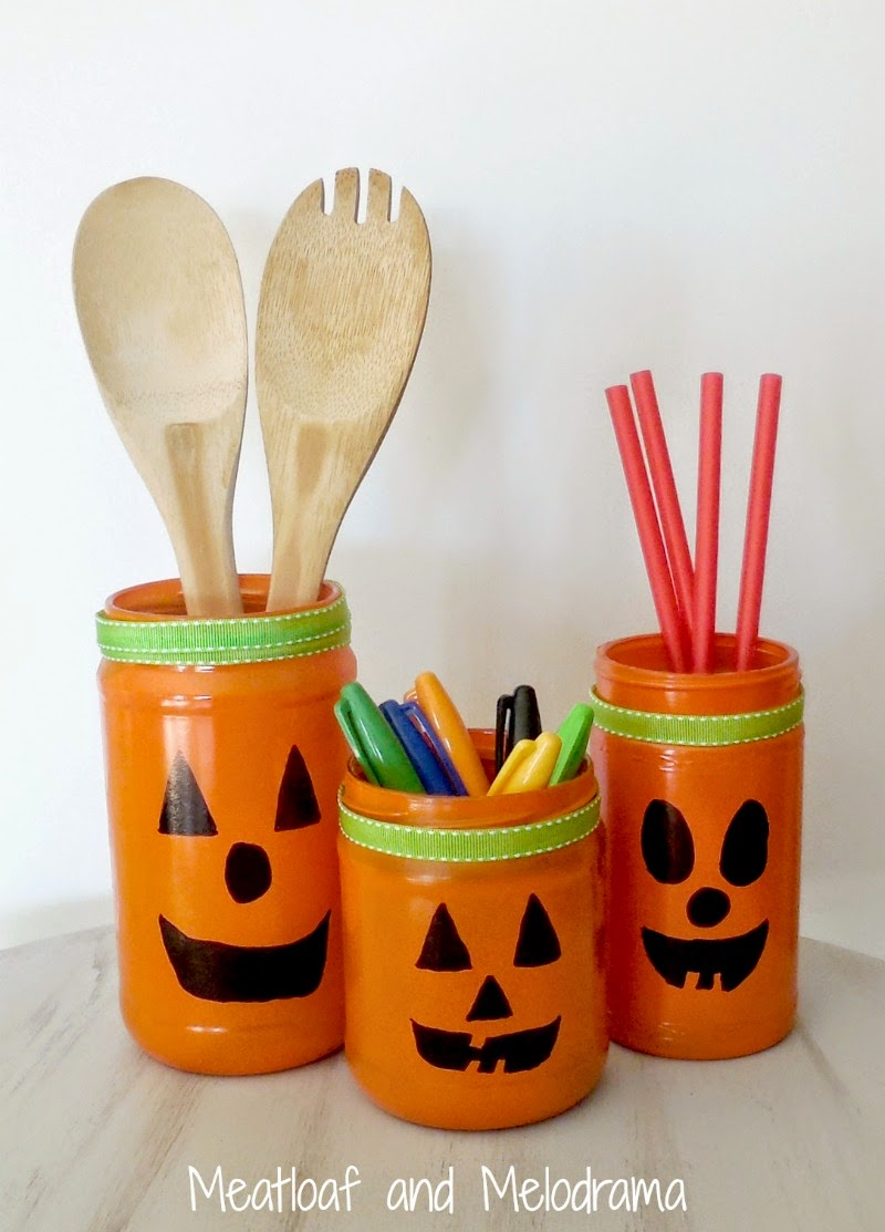 three glass jars spray painted orange to use as containers for sharpies, spoons and straws for halloween