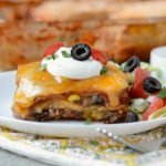 southwestern lasagna enchilada casserole on plate with sour cream lettuce tomatoes and olives