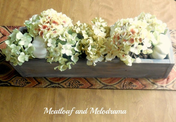 distressed wood box with fall flowers, pinecones and white pumpkins