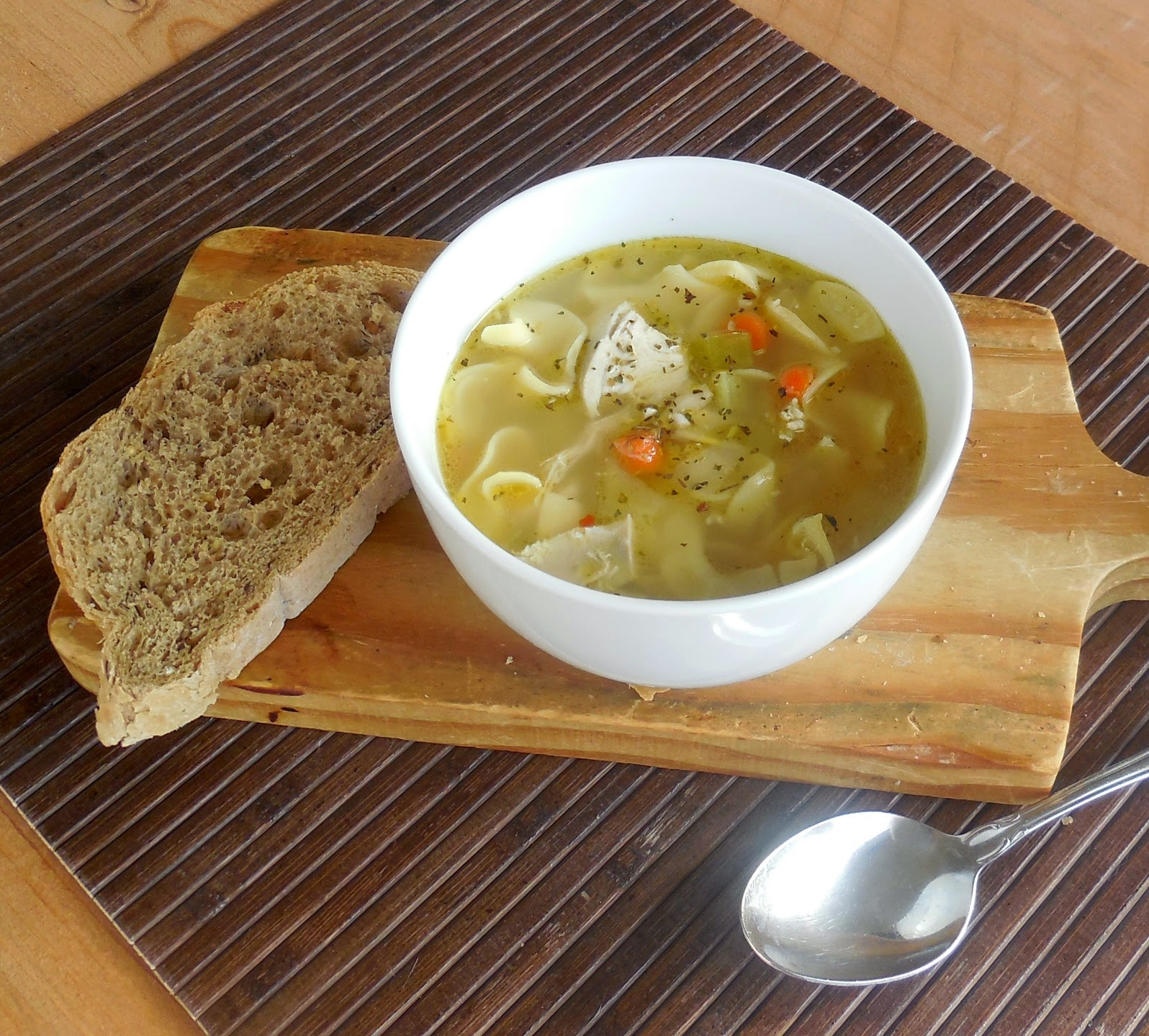 bowl of chicken soup with egg noodles and bread