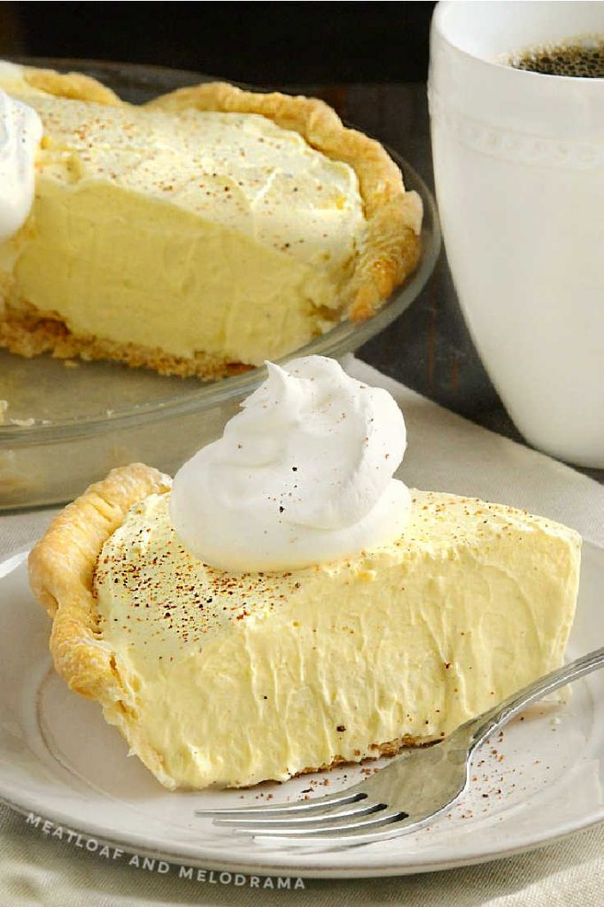 slice of eggnog pie with whipped topping and pie in backgraound