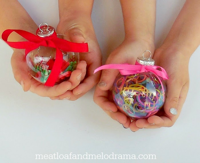 kids holding clear plastic ornaments filled with legos and loom bands and ribbons
