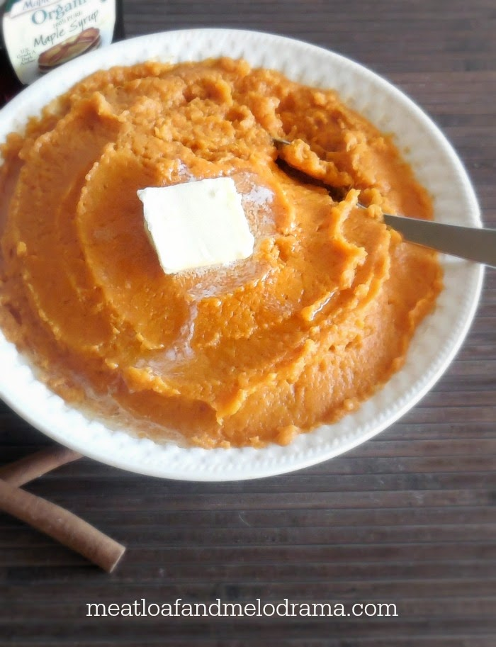 bowl full of mashed sweet potatoes with butter cinnamon and maple syrup