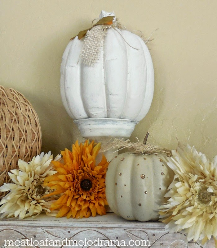 white pumpkin on white candlestick with mums and rhinestone pumpkin