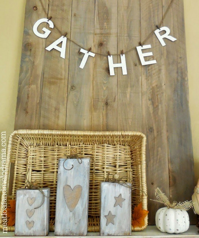 rustic wood board with gather garland and primitive wood pumpkins