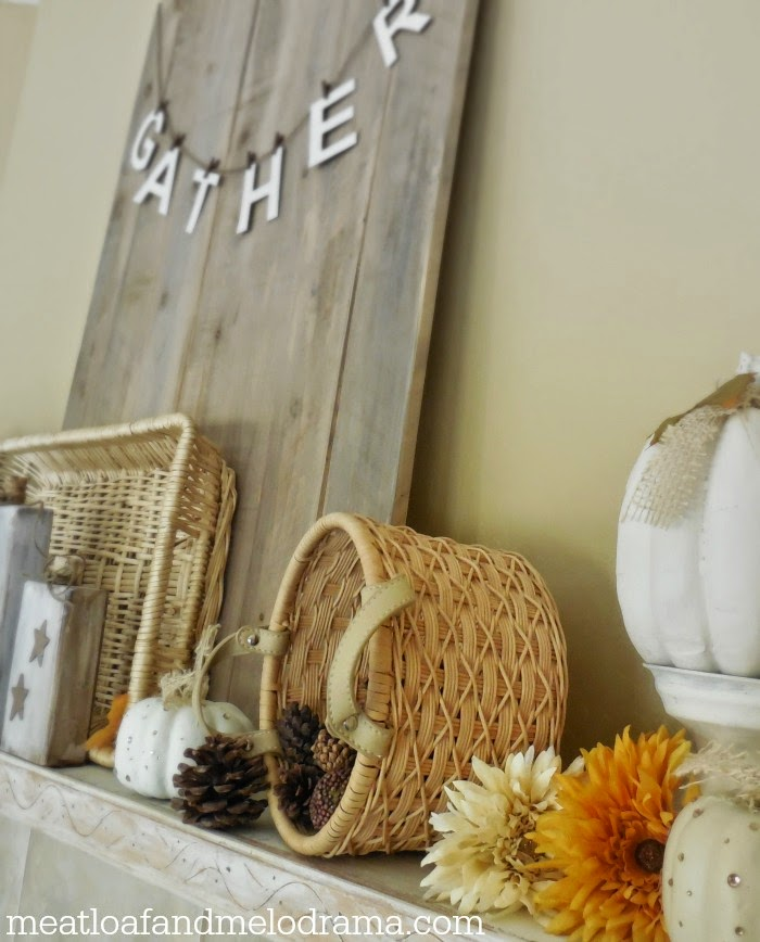 fireplace mantel decorated with baskets mums white pumpkins and wood board with gather
