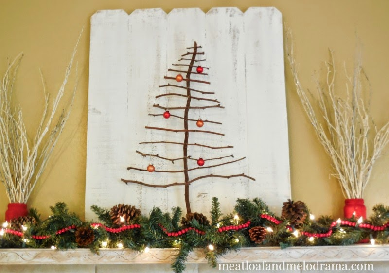 mantel decorated with rustic natural elements like branches twig tree and pine cones and white wood backdrop