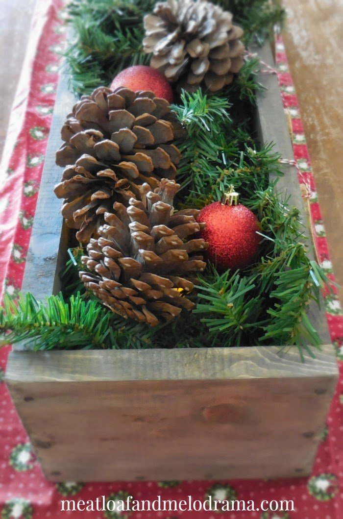 wooden box with pine cones, pine garland and red ornaments