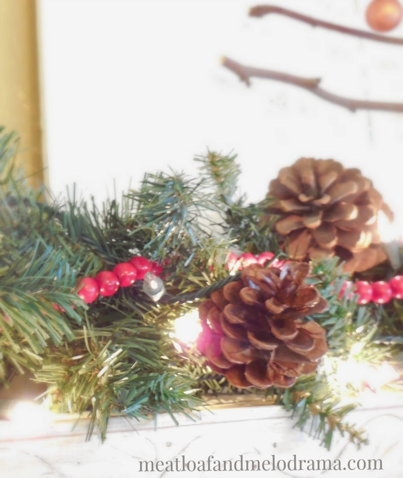 pine cones and lights and red wood beads on mantel