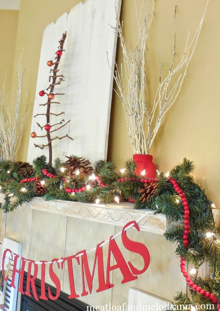 pine garland red beads twig tree and painted branches on mantel