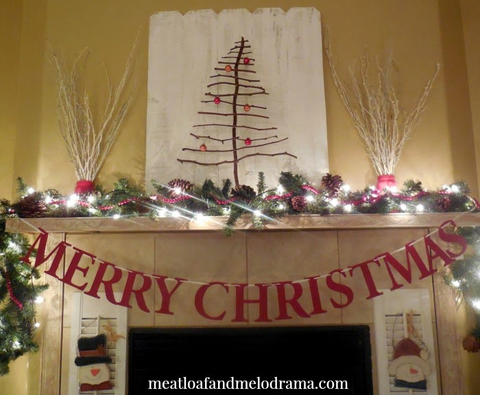 twig tree and merry christmas banner and pine garland on rustic mantel