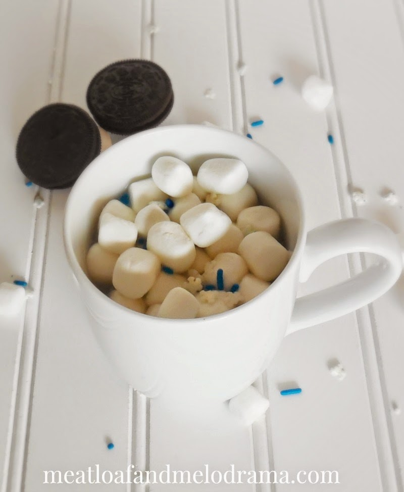 cup of hot chocolate with marshmallows and cookies and candy sprinkles