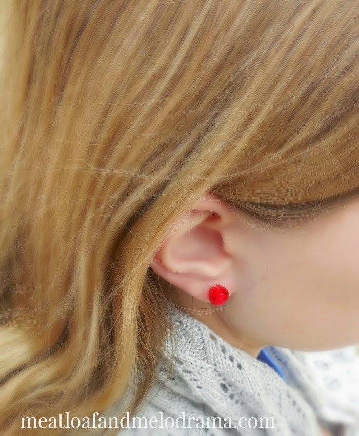 girl wearing red lego earrings