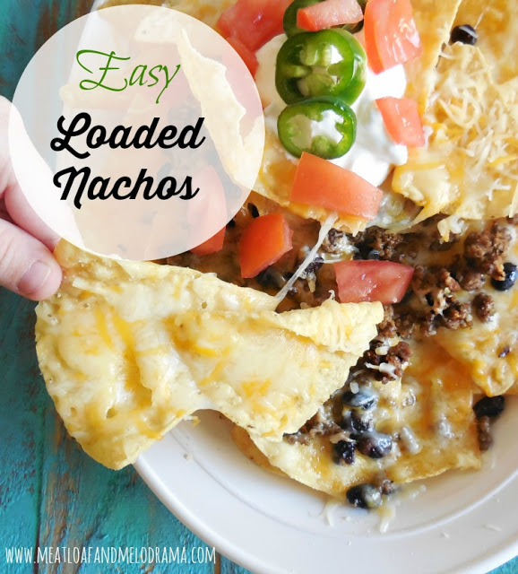 loaded nachos with cheese and meat and black beans and tomatoes