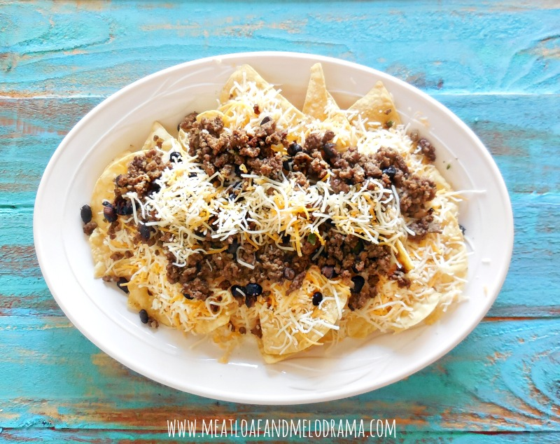 nachos made with layers of ground beef and beans and cheese