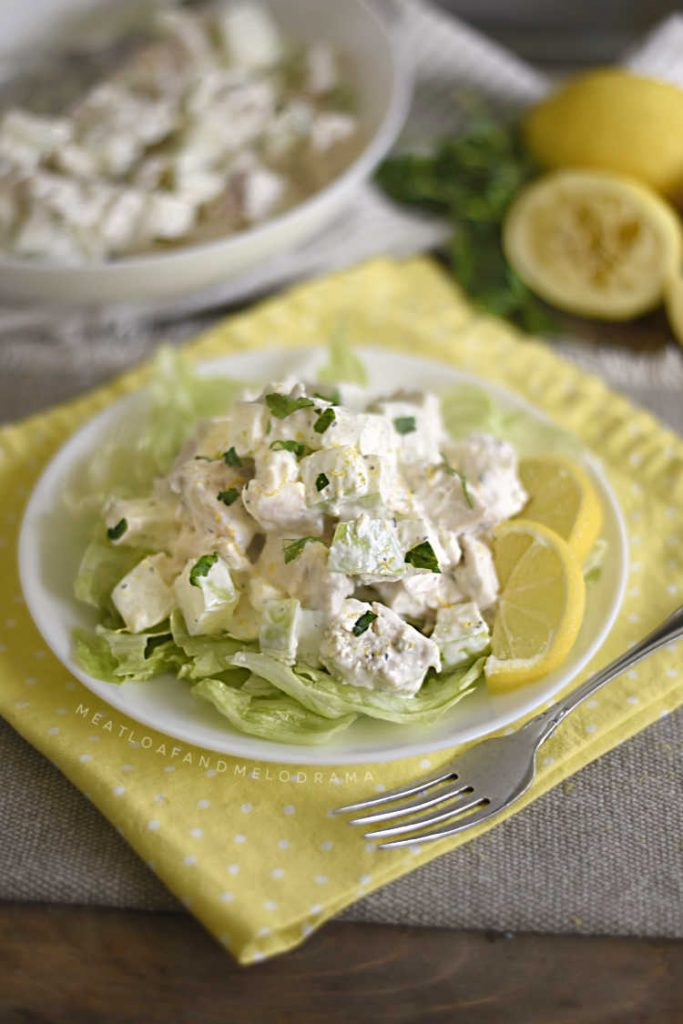 lemon chicken salad with apples and lemon slices over iceberg lettuce