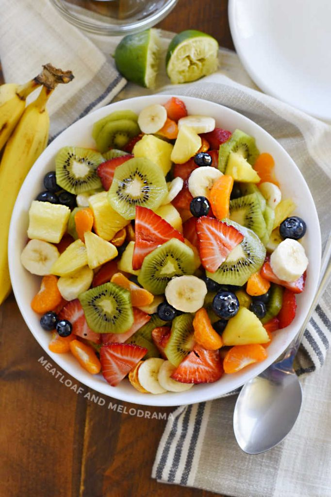 cut up summer fruit in a white serving bowl