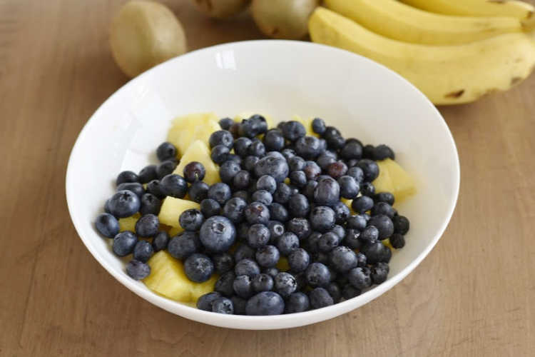 blueberries and pineapple chunks in white bowl