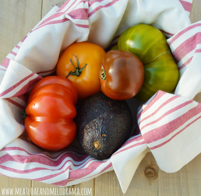basket of heirloom tomatoes and avocado