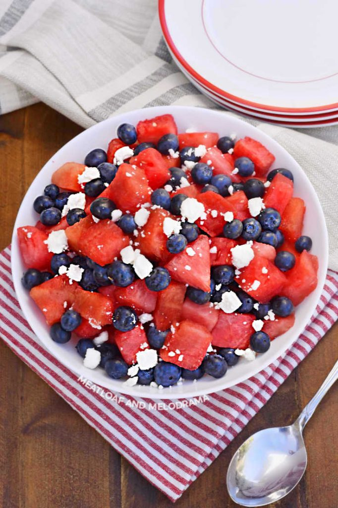 bowl of cut up watermelon, blueberries and feta cheese crubmles