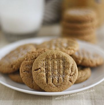 flourless peanut butter cookies on a white plate with glass of milk