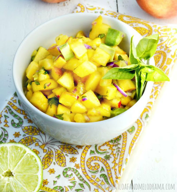 bowl of fresh peach salsa with avocado red onions and basil