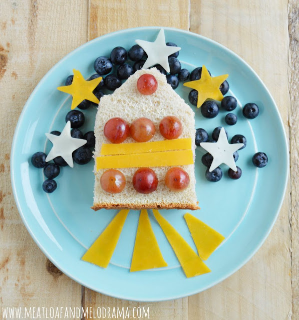 rocket space ship sandwich art made from bread with blueberries and grapes and cheese