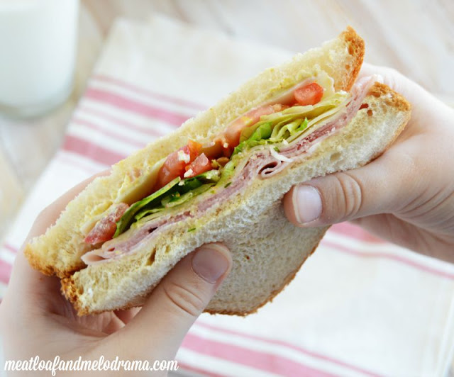 ham sandwich with lettuce and provolone and tomatoes