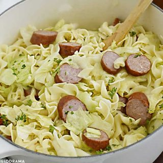 haluski and kielbasa, fried cabbage with noodles and smoked sausage in a white dutch oven