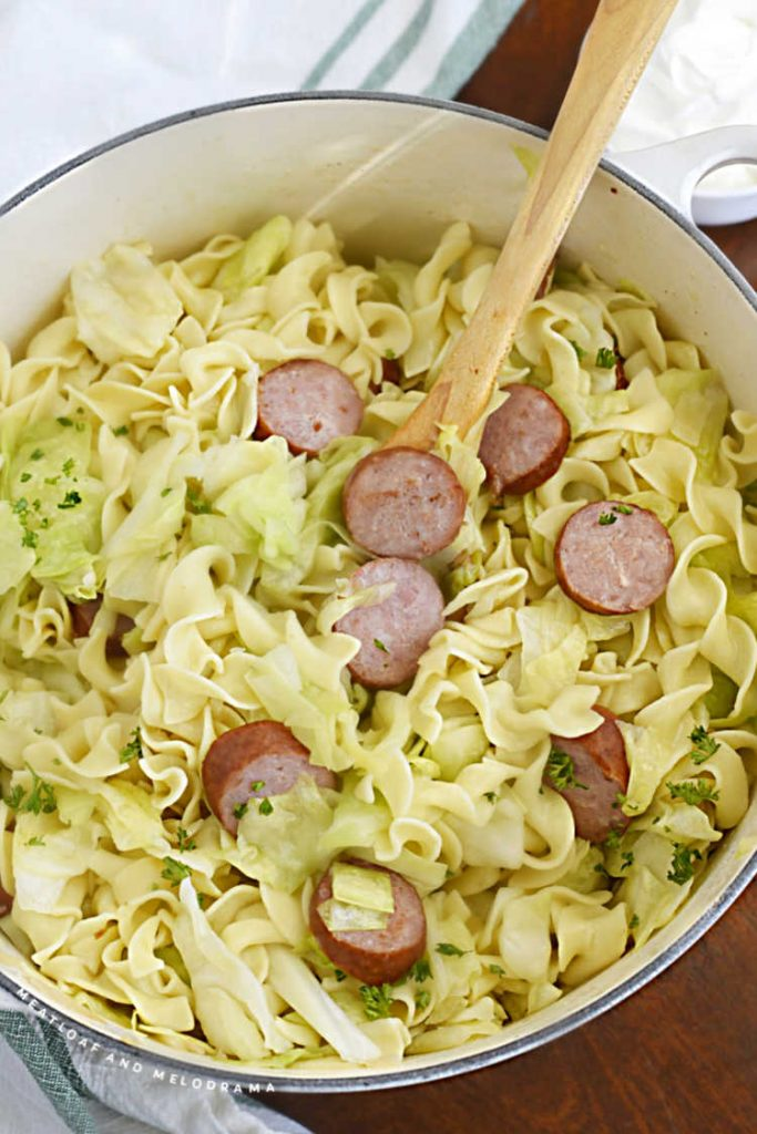 cabbage, noodles and kielbasa with wooden spoon in a dutch oven