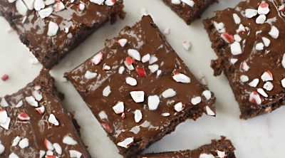 overhead view of sliced peppermint brownies with chocolate and crushed peppermint candies on white marble