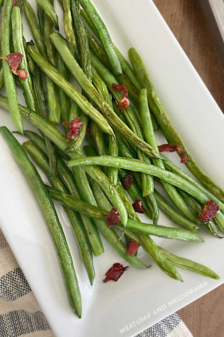 easy sauteed green beans with bacon and parmesan cheese on platter