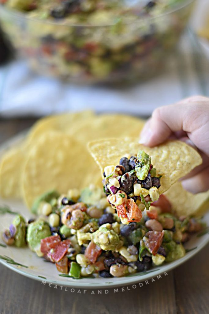 cowboy caviar on a tortilla chip in hands