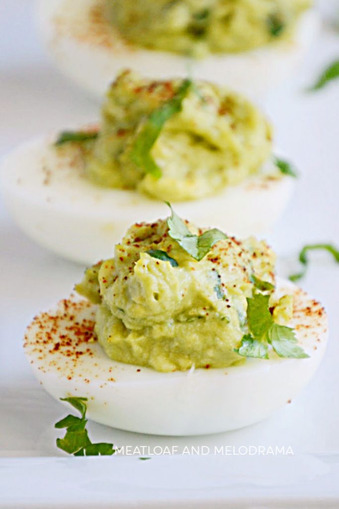 guacamole deviled eggs on a serving tray