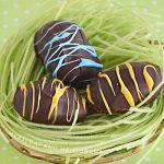 chocolate covered peanut butter eggs with yellow and blue stripes in a bowl with edible Easter grass